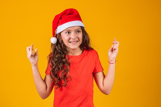 Portrait of a little girl dressed in christmas outfit with her fingers crossed wishing her luck.