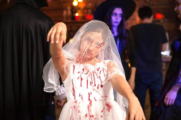 Portrait of little girl dressed up like a bride covered with blood at halloween party. girl with creepy expression.