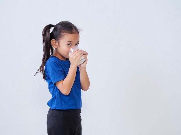 Portrait of little girl drinking milk from glass on light
