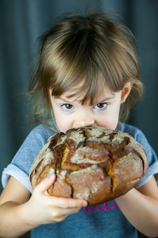 Portrait of a little girl eating a big crunchy circle rye bread, she's very hungry