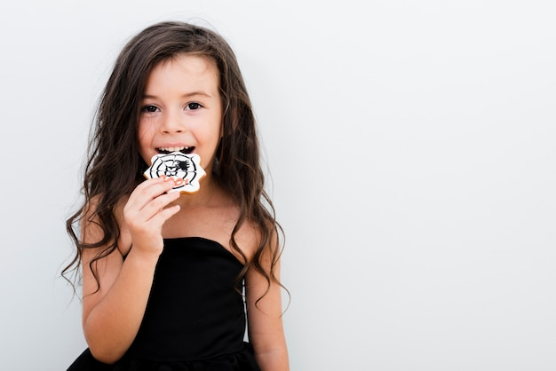 Portrait of a little girl eating a cookie
