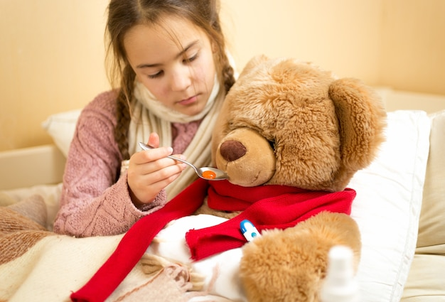 Portrait of little girl giving medicines to teddy bear