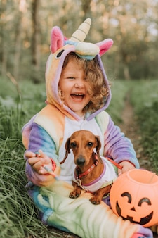 Portrait of little girl and a do in halloween costumes with a pumpkin basket for sweets outdoors