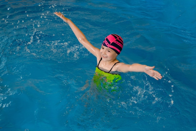 Portrait of a little girl having fun in indoor swimming pool