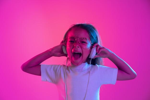 Portrait of little girl in headphones on purple gradient