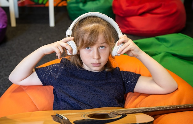 Portrait of a little girl in headphones and with a guitar in the process of learning music