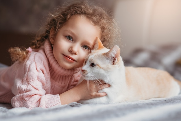 Portrait of a little girl and her pet cat lying on the bed