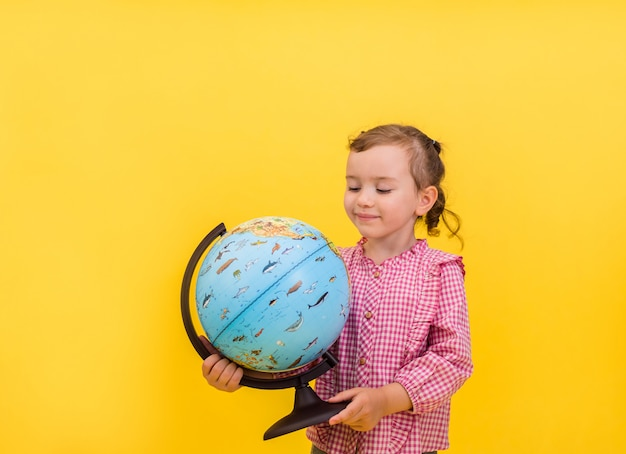 Portrait of a little girl holding a globe in her hands on a yellow isolated background with space for text.