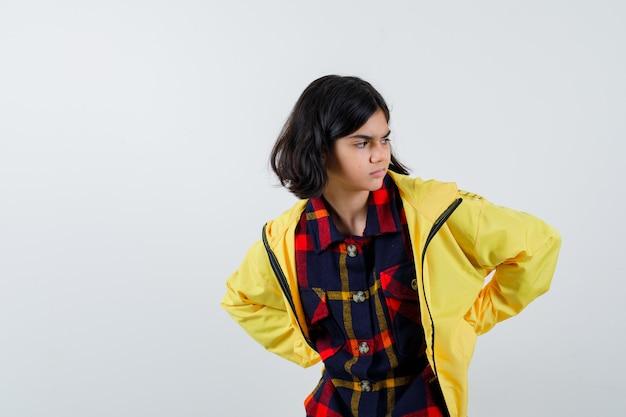 Ritratto di bambina tenendo la mano dietro la schiena in camicia a quadri, giacca e guardando premurosa vista frontale Foto Gratuite