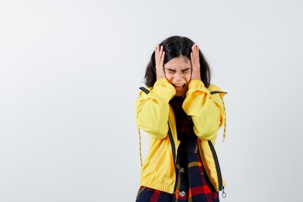 Ritratto di bambina tenendo le mani sulla testa in camicia a quadri, giacca e guardando confuso vista frontale