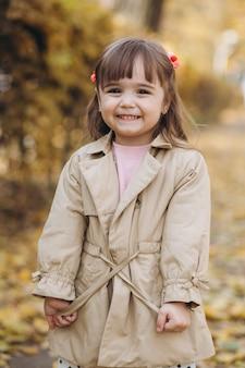 ベージュのコートを着た肖像画の少女が秋の公園を歩く