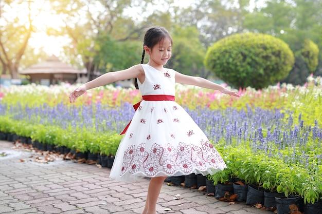 庭の周りの花でリラックスした白いドレスの少女の肖像画。
