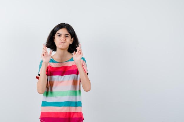 Ritratto di bambina che tiene le dita incrociate in maglietta e sembra una vista frontale senza speranza
