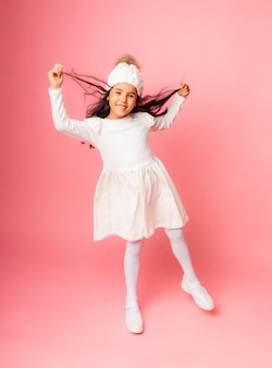 Portrait of a little girl in a knitted white winter hat and white dress on a pink background