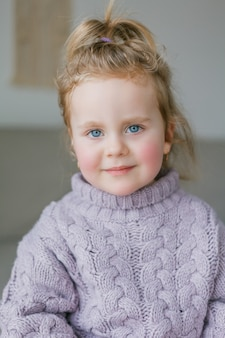 Portrait of a little girl in a lilac knitted sweater. happy child. cozy.