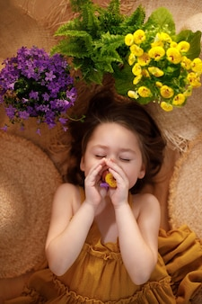 Portrait of a little girl lying from straw hats holding flowers in hands, summer and travel feeling concept