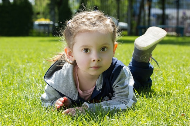 Portrait of a little girl lying on green grass. cute three years old child enjoying nature park.