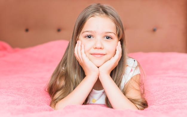 Portrait of a little girl lying on pink blanket sheet on bed