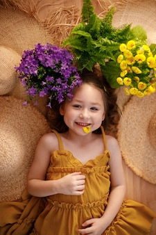 Portrait of a little girl lying with flowers and straw hat, summer and travel feeling concept.