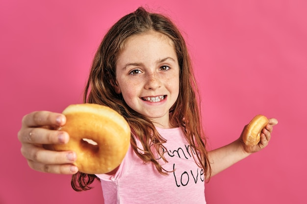 Portrait of a little girl offering a donut on a pink background