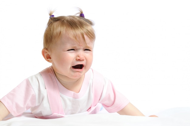 Portrait of a little girl in pink clothes crying