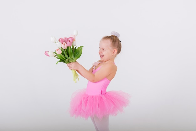 Portrait of a little girl in a pink dress giving a bouquet of tulip flowers on a white wall