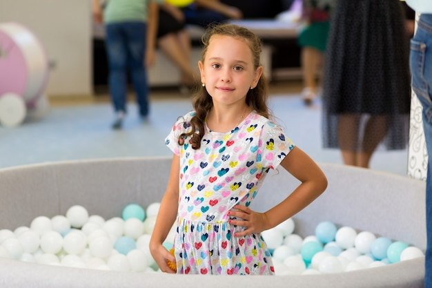 Portrait of a little girl playing in the pool with plastic balls
