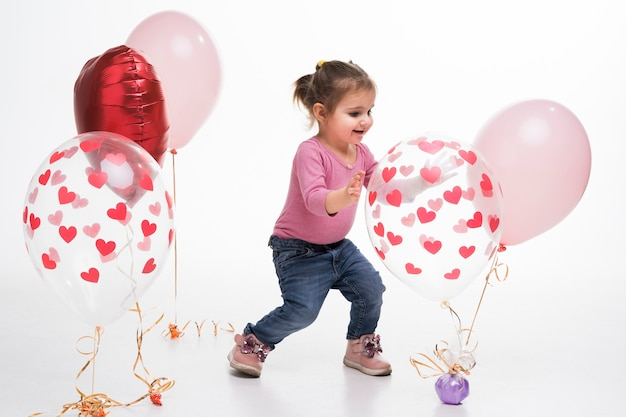 Portrait of little girl playing with balloons