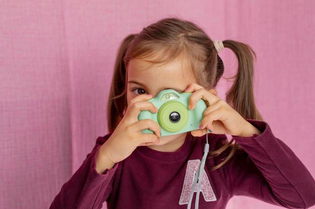 Портрет маленькой девочки, играющей с камерой