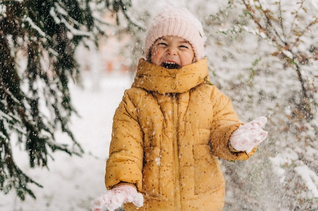 Portrait of a little girl playing with snow