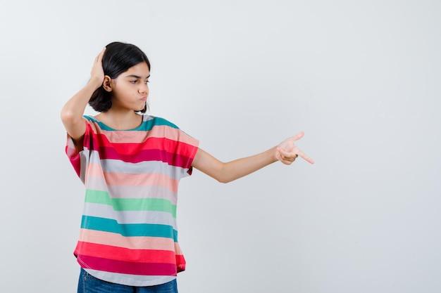 Ritratto di bambina che punta verso il basso, tenendo la mano sulla testa in maglietta e guardando la vista frontale pensierosa