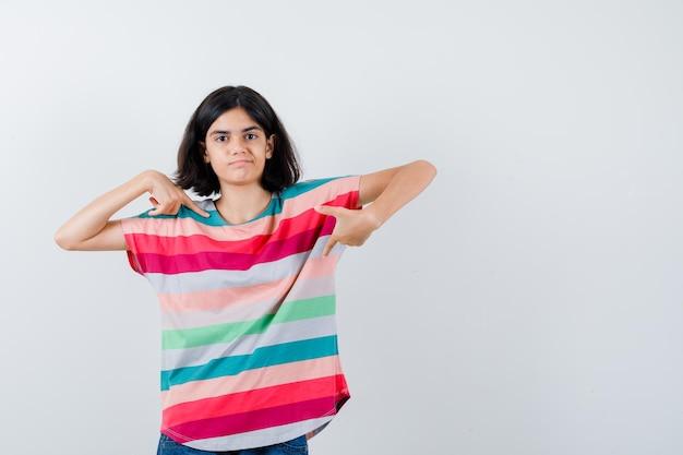 Ritratto di bambina che indica se stessa in maglietta e guarda fiduciosa vista frontale