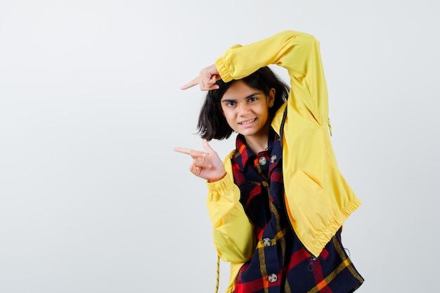 Ritratto di bambina che punta verso il lato sinistro in camicia a quadri, giacca e guardando la vista frontale positiva
