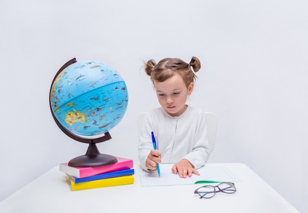 Portrait of a little girl pupil writing with a pen in a notebook at a table on a white isolated