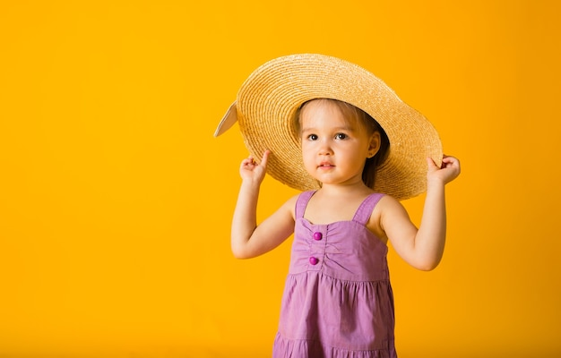 Portrait of a little girl in a purple sundress and straw hat on a yellow surface with space for text