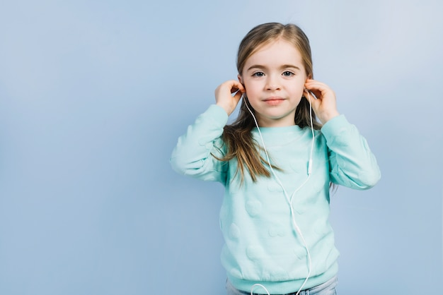 Portrait of a little girl putting earphones on her ears against blue background