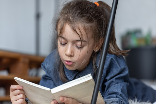 Portrait of a little girl reading a book lying on the floor in the room.