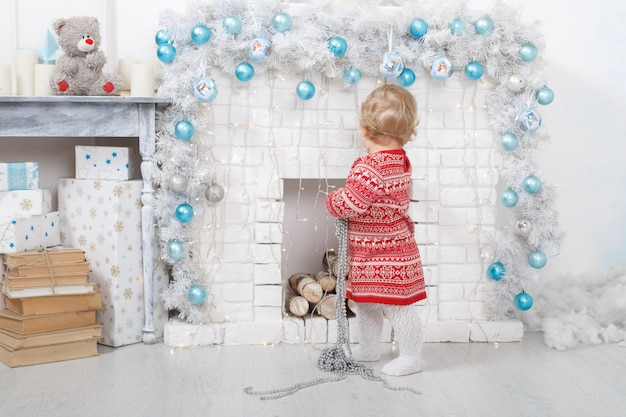Portrait a little girl  in a red dress near a  brick fireplace in christmas decorated home. christmas  holidays indoors with toys and gift box