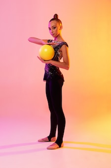 Portrait of little girl, rhythmic gymnastics artist training isolated on colored