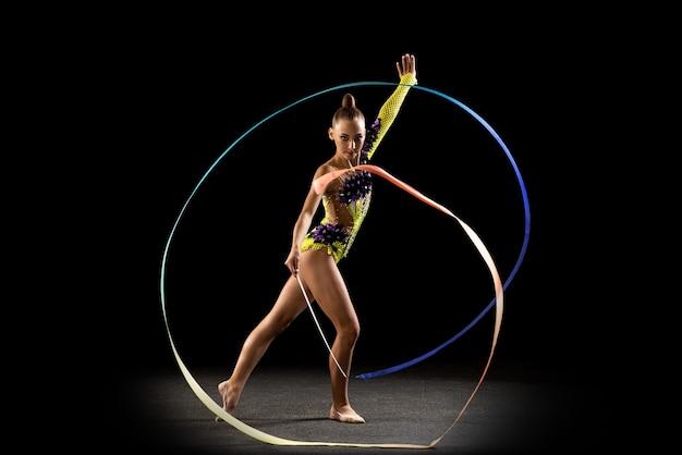 Portrait of little girl, rhythmic gymnastics artist training isolated on dark