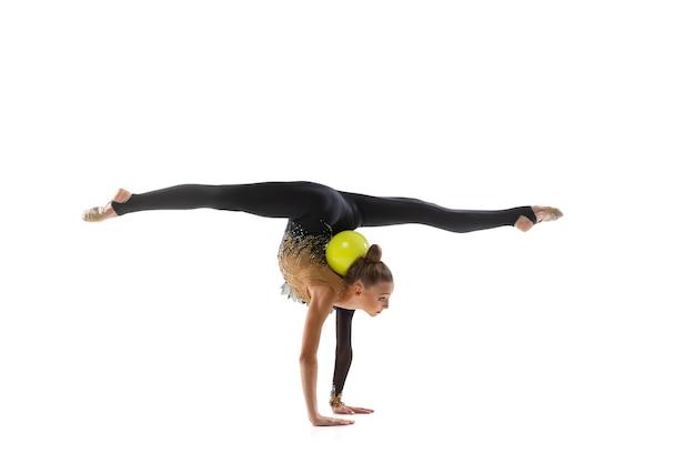 Portrait of little girl, rhythmic gymnastics artist training isolated on white