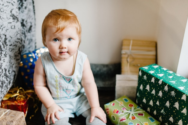 Portrait of a little girl in room sits and unpacks gifts. festive birthday concept