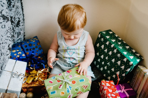 Portrait of a little girl in room sits and unpacks gifts. festive birthday concept.