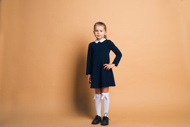 Portrait of  little girl in school uniform isolated on brown.