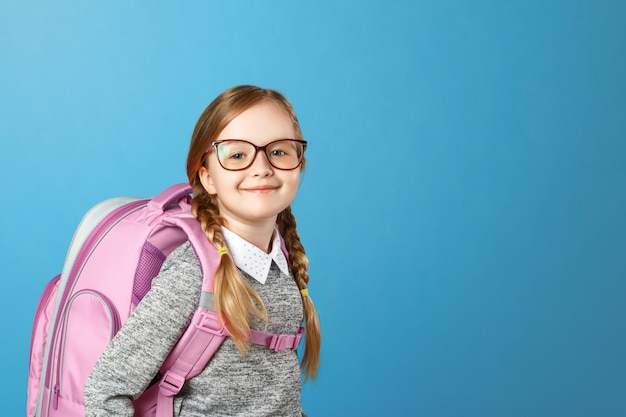 Portrait of a little girl schoolgirl with a backpack on a blue background