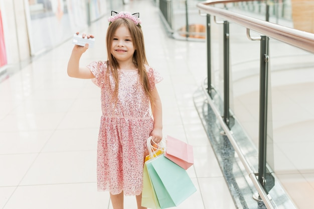 Portrait of a little girl in a shopping center with a credit card in hand. cute baby smiling. online shopping concept