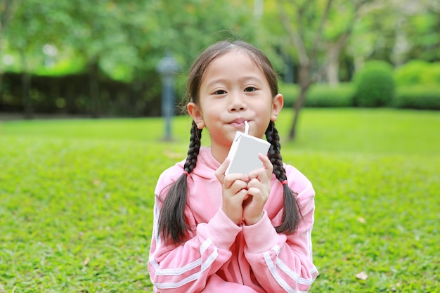 Portrait of little girl in sport cloth drinking milk from box with straw in the nature park.