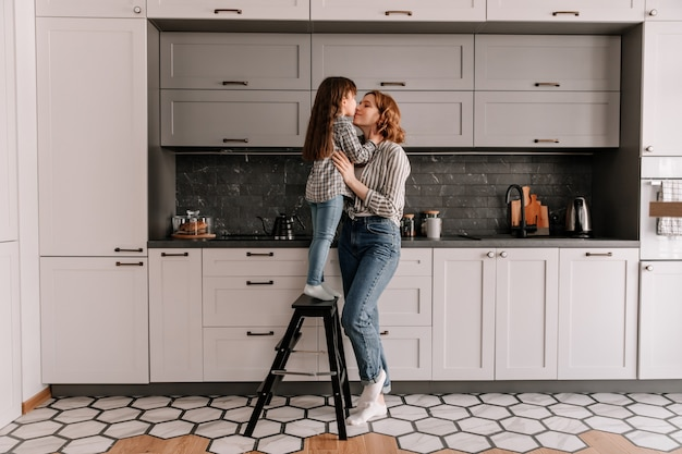 Portrait of little girl stands on stairs and hugs mother in kitchen.