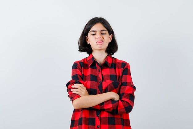 Portrait of little girl sticking out tongue while standing with crossed arms