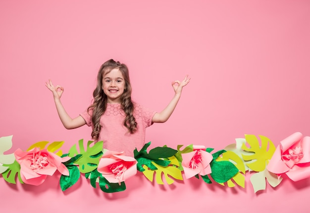 Portrait of a little girl on a summer pink wall